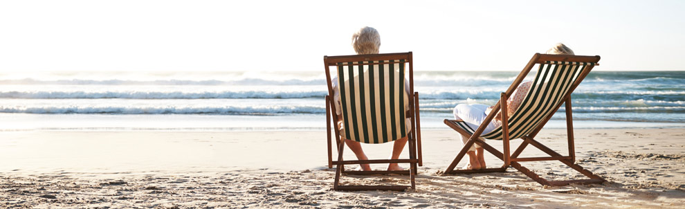 Older couple sitting on the beach in chairs